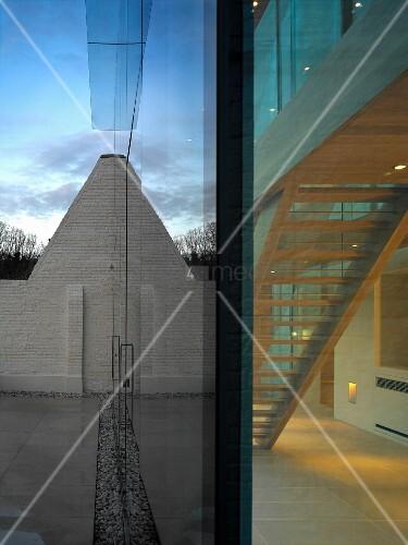 Terrasse Vor Glasfront Eines Zeitgenössischen Hauses Mit Blick In  Beleuchteten Treppenraum