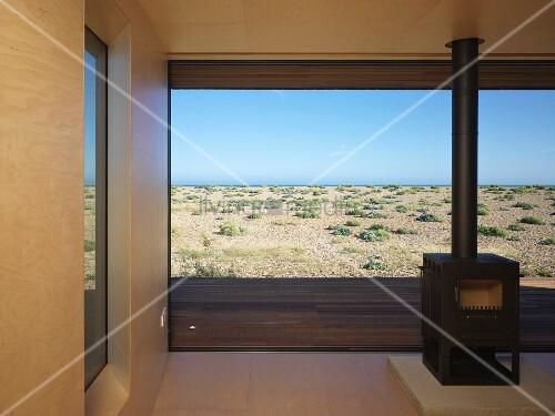freistehender kaminofen vor raumhohem terrassenfenster mit meerblick bild kaufen living4media. Black Bedroom Furniture Sets. Home Design Ideas