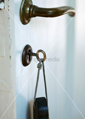 schl ssel mit anh nger steckt im schl sselloch bild. Black Bedroom Furniture Sets. Home Design Ideas