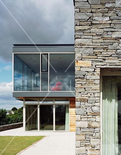 haus mit steinmauer und verglastem anbau bild kaufen. Black Bedroom Furniture Sets. Home Design Ideas