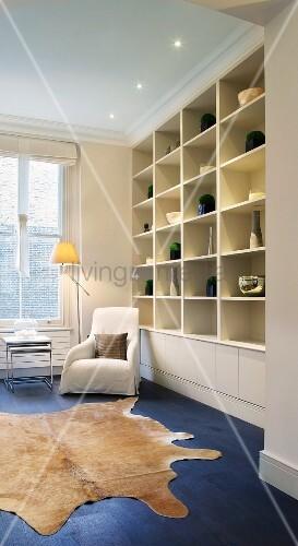 moderne sitzecke mit tierfell vor einbauregal mit sammlung. Black Bedroom Furniture Sets. Home Design Ideas