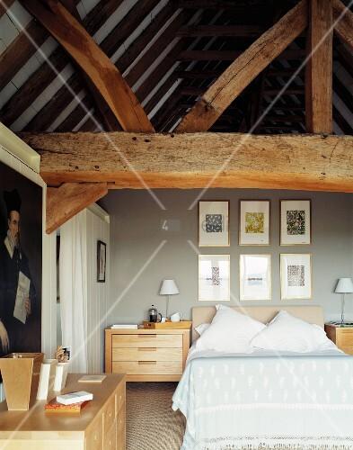 modernes schlafzimmer mit hellen holzm beln unter massiven alten dachbalken bild kaufen. Black Bedroom Furniture Sets. Home Design Ideas