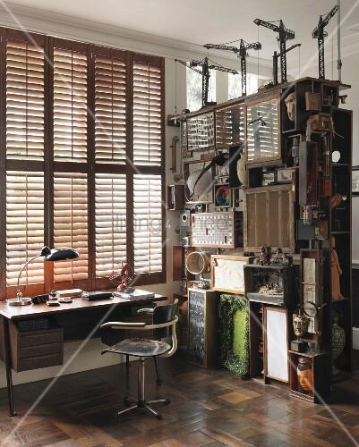 arbeitsplatz im vintagestil vor fenster mit geschlossenen l den und regal mit sammelsurium. Black Bedroom Furniture Sets. Home Design Ideas