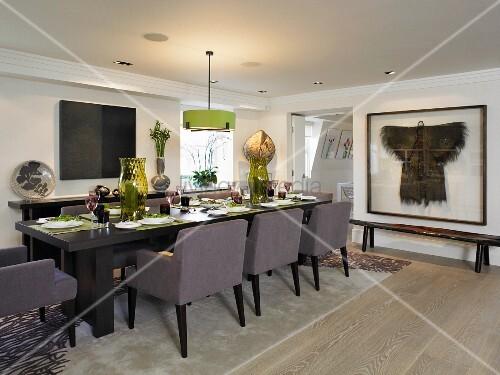 festlich gedeckter tisch mit gepolsterten st hlen im modernen esszimmer bild kaufen living4media. Black Bedroom Furniture Sets. Home Design Ideas