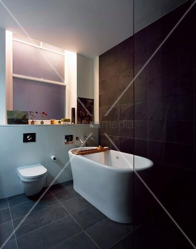 freistehende badewanne auf grauen bodenfliesen vor dunkelgrauer wand bild kaufen living4media. Black Bedroom Furniture Sets. Home Design Ideas