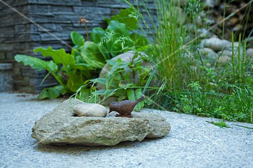 steine und vogelfigur aus metall auf den natursteinfliesen der terrasse bild kaufen living4media. Black Bedroom Furniture Sets. Home Design Ideas