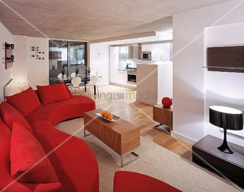 rote geschwungene couch und tischm bel aus holz im offenen wohnraum bild kaufen living4media. Black Bedroom Furniture Sets. Home Design Ideas