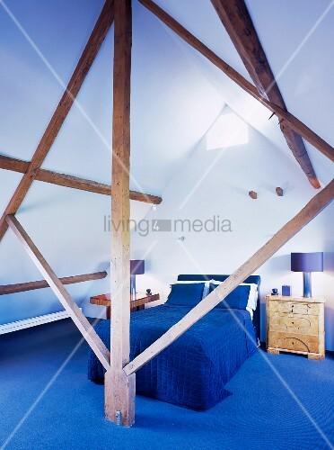 blick durch holzkonstruktion auf bett mit blauer tagesdecke und blauem teppichboden unter dem. Black Bedroom Furniture Sets. Home Design Ideas