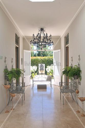 st hle aus metall auf marmorboden im vorraum eines landhauses und offen stehende terrassent r. Black Bedroom Furniture Sets. Home Design Ideas