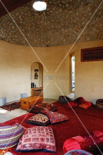 Bunte, indische Kissen auf rotem Teppich in Meditationsraum mit ...