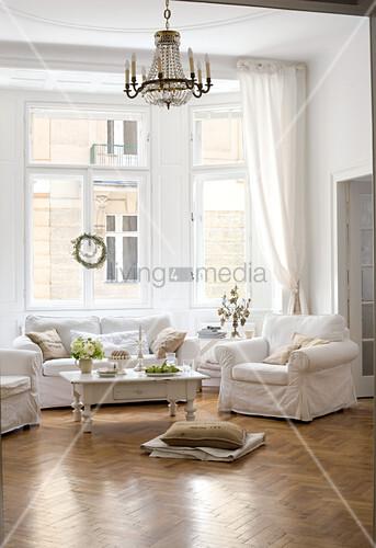 sofagarnitur mit weissen hussen und couchtisch unter kronleuchter im wohnzimmer erker einer. Black Bedroom Furniture Sets. Home Design Ideas