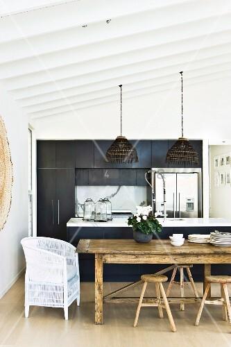 weisser rattanstuhl und rustikale hocker um esstisch vor offener k che in schwarz bild kaufen. Black Bedroom Furniture Sets. Home Design Ideas