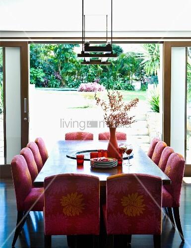 gepolsterte st hle mit gemustertem bezug am esstisch vor. Black Bedroom Furniture Sets. Home Design Ideas