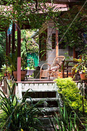 b sche und gr ser vor holzhaus mit sonnenbeschienener veranda und rattansessel bild kaufen. Black Bedroom Furniture Sets. Home Design Ideas