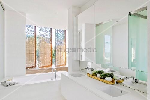Puristisches Badezimmer mit Doppelwaschtisch und Badewanne vor drehbaren Rattanelementen als ...