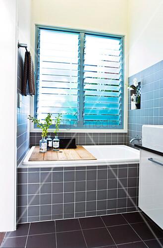 gro es badezimmerfenster mit jalousien darunter eine eingebaute badewanne mit h lzerner ablage. Black Bedroom Furniture Sets. Home Design Ideas