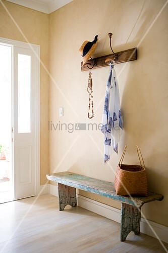 offene garderobe mit hut und tuch an wand befestigt ber rustikaler holzbank in schlichtem. Black Bedroom Furniture Sets. Home Design Ideas