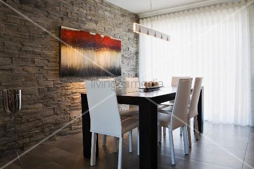 weisse lederst hle an schwarzem tisch gegen ber natursteinwand und transparentem vorhang in. Black Bedroom Furniture Sets. Home Design Ideas