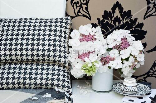 weisse hortensien in kleiner vase neben dekokissen vor geflockter brokattapete bild kaufen. Black Bedroom Furniture Sets. Home Design Ideas