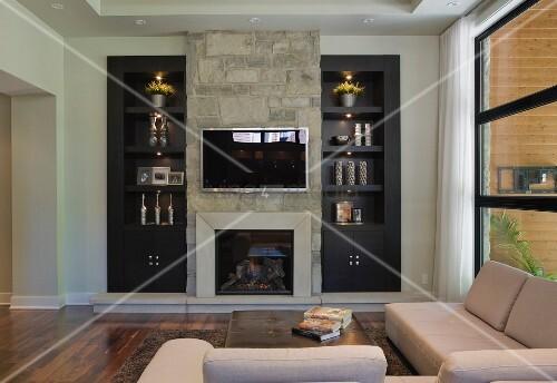 Wohnzimmerwand mit eingebautem Kamin und Fernseher – living4media