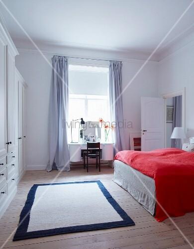 rote tagesdecke auf bett in weissem schlafzimmer bild kaufen living4media. Black Bedroom Furniture Sets. Home Design Ideas