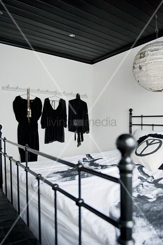 metallbett im antikstil unter schwarzer holzdecke mit japanballon lampe und schwarze. Black Bedroom Furniture Sets. Home Design Ideas
