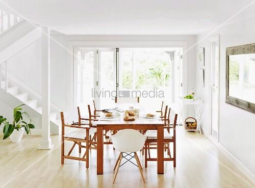 esstisch aus holz mit passenden st hlen vor terrassenfenster in offenem weissem wohnraum mit. Black Bedroom Furniture Sets. Home Design Ideas