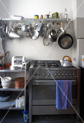 moderner gasherd mit edelstahlfront neben rolltisch und wandbord mit aufgeh ngtem kochgeschirr. Black Bedroom Furniture Sets. Home Design Ideas