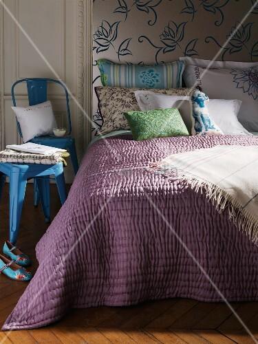 doppelbett mit gesteppter tagesdecke und verschiedenen kissen in schlafzimmer bild kaufen. Black Bedroom Furniture Sets. Home Design Ideas