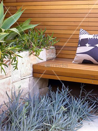 sitzbank und r ckwand aus holz neben mediterranen pflanzen im hochbeet mit natursteinmauer. Black Bedroom Furniture Sets. Home Design Ideas