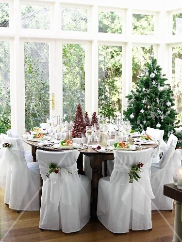 festlich gedeckter weihnachtstisch im wintergarten mit st hlen in eleganten stoffhussen bild. Black Bedroom Furniture Sets. Home Design Ideas