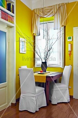 kr ftiger gelbton in wohnzimmerecke mini sitzecke mit sesseln und weisser husse am holztisch. Black Bedroom Furniture Sets. Home Design Ideas
