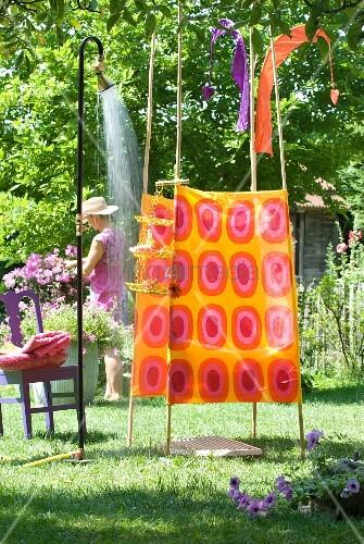 umkleidezelt aus stoff mit 70er jahre muster in pink und orange vor laufender gartendusche. Black Bedroom Furniture Sets. Home Design Ideas