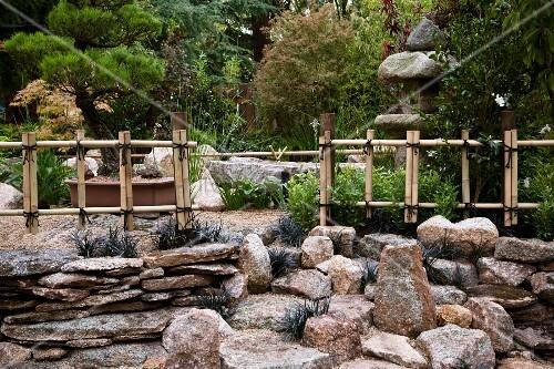 japanischer steingarten mit verschn rten bambus z unen und steinlampe im hintergrund bild. Black Bedroom Furniture Sets. Home Design Ideas