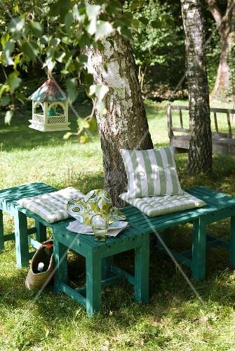 kleine sitzgruppe aus gr nen holzb nken mit gestreiften kissen vor einer birke bild kaufen. Black Bedroom Furniture Sets. Home Design Ideas