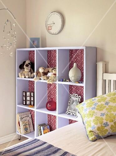 kinderzimmer bett neben fliederfarbenem regal mit stofftieren und vasen dar ber eine uhr an. Black Bedroom Furniture Sets. Home Design Ideas