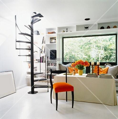 stuhl mit orangem sitzpolster vor tisch mit husse und wendeltreppe aus schwarz lackiertem metall. Black Bedroom Furniture Sets. Home Design Ideas