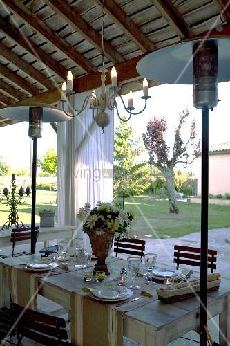 festlich gedeckter tisch auf berdachter terrasse mit gaspilzheizung und blick in garten bild. Black Bedroom Furniture Sets. Home Design Ideas