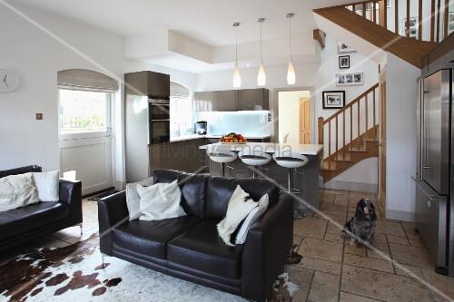 ledersofas auf kuhfellteppich in offenem wohnraum mit. Black Bedroom Furniture Sets. Home Design Ideas