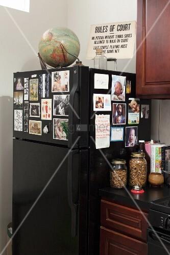 Schwarzer Kühlschrank mit Fotos dekoriert, oberhalb Globus und ...