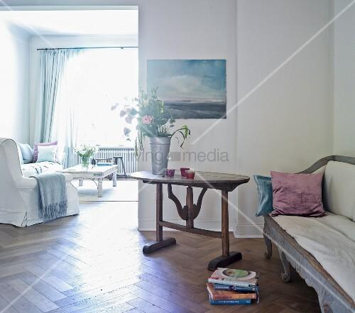 Wohnzimmer mit antikem sofa und rustikalem tisch im for Sofa vor fenster