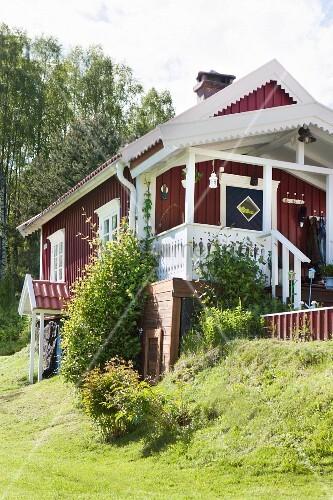 schwedisches holzhaus mit weissen giebelbrettern in l ndlicher umgebung bild kaufen living4media. Black Bedroom Furniture Sets. Home Design Ideas