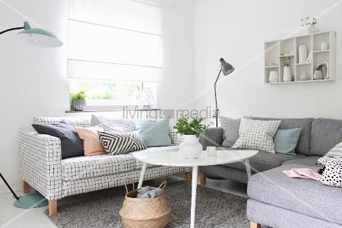 Wohnzimmerecke mit weissem couchtisch und sofas mit for Sofa vor fenster
