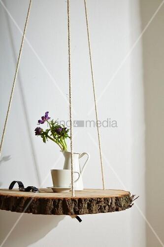 Hängender Nachttisch rustikale baumscheibe an seilen aufgehängt als nachttisch bild