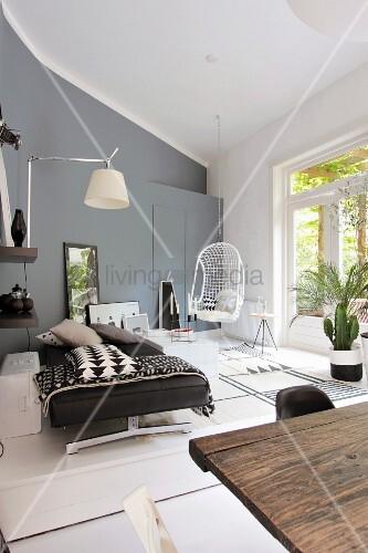 modernes wohnzimmer in grautnen mit tagesbett hngestuhl wandleuchte und pflanzen im vodergrund rustikaler holztisch - Modernes Tagesbettgestell