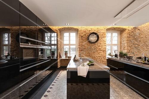 moderne k che mit schwarzen hochglanzoberfl chen und freistehenden theken sandsteinw nde mit. Black Bedroom Furniture Sets. Home Design Ideas