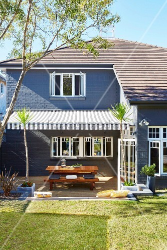 haus mit garten und sitzplatz unter gestreifter markise bild kaufen living4media. Black Bedroom Furniture Sets. Home Design Ideas