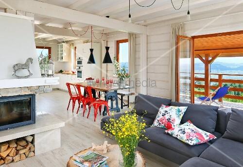 gro er wohnraum mit sofa esstisch und offener k che im holzhaus bild kaufen living4media. Black Bedroom Furniture Sets. Home Design Ideas