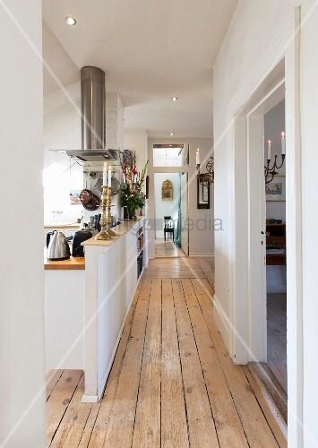 Flur mit Holzdielen und offener Küche hinter halbhoher Wand – Bild ...