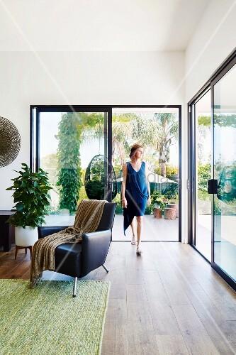 eleganter wohnbereich mit schwarzem ledersessel und terrassenverglasung frau vor. Black Bedroom Furniture Sets. Home Design Ideas